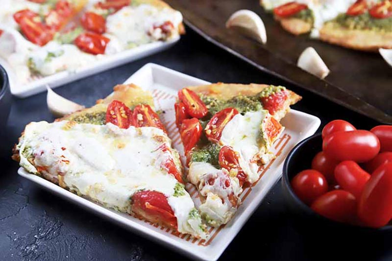 A close up of a white square dish with two slices of pizza with parsley pesto and mozzarella cheese. To the right of the frame is a small bowl of cherry tomatoes.