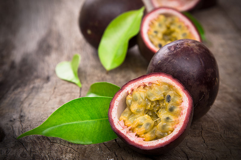 A close up of a ripe passion fruit cut in half showing the seeds and pulp, set on a wooden surface with leaves scattered around.