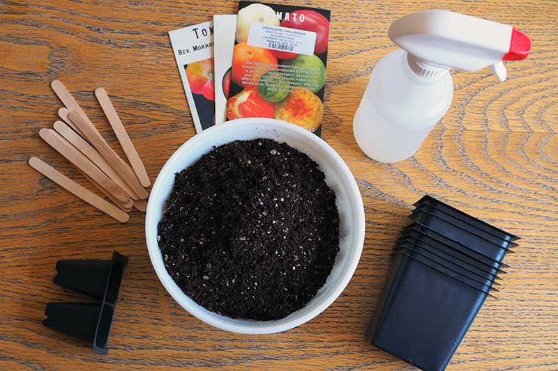 A top down picture of some gardening supplies needed to start vegetable seeds, including pots, soil, a misting bottle, and plant markers set on a wooden surface.