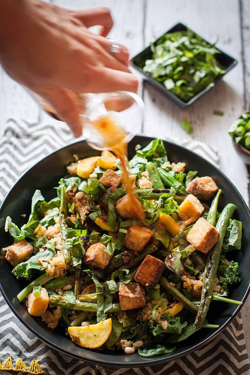 A close up vertical picture of a hand from the left of the frame holding a small glass carafe pouring dressing onto a tofu and bean salad in a black bowl set on a wooden surface. In the background is a small bowl of salad in soft focus.
