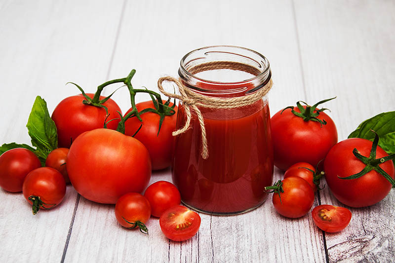 A close up of a glass jar filled with tomato juice set on a wooden surface, surrounded by fresh fruit, recently harvested.