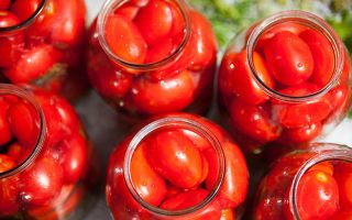 A close up top down picture of glass jars containing freshly harvested tomatoes, pictured in bright sunshine on a soft focus background.