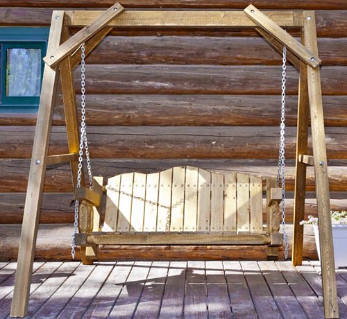 A close up of a wood-framed hanging bench seat outside a log cabin, pictured in bright sunshine.