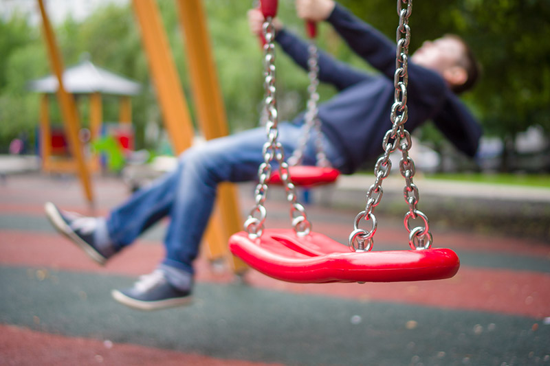 A close up of a red swing with a plastic seat and metal chains with a child in soft focus in the background.