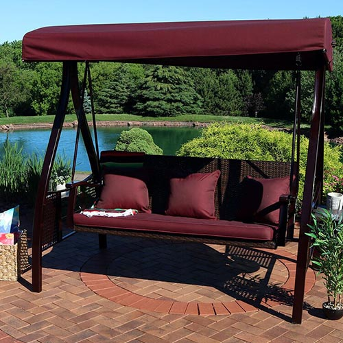 A standalone, metal-framed porch swing with a maroon canopy and cushions set outdoors on a brick patio with a lake view in the background.