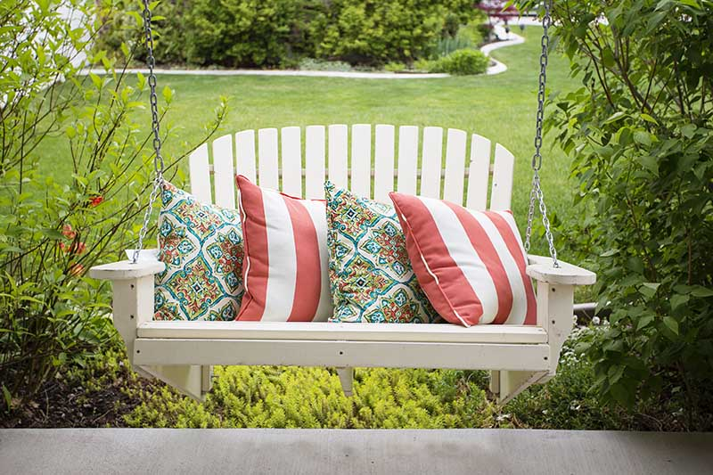 A close up of a white hanging bench overlooking a summer garden scene with lawns and shrubs in the background.
