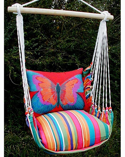 A close up of a hanging hammock chair with brightly colored cushions with foliage in the background.