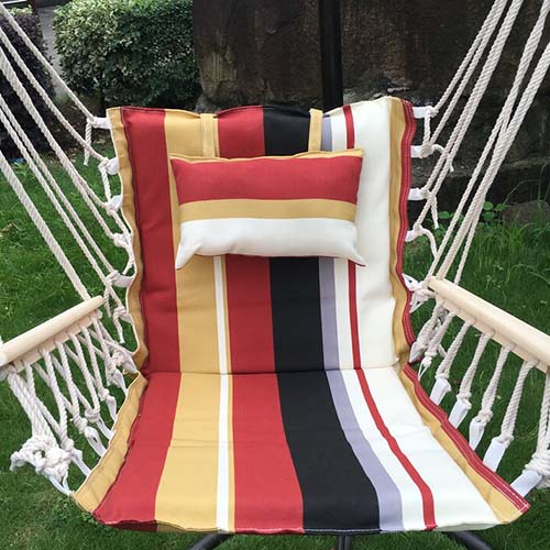 A close up of a chair hammock with colorful striped cushions hanging in the garden with trees in soft focus in the background.