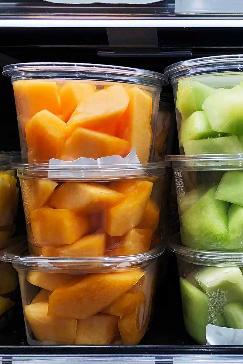 A vertical picture of plastic tubs containing fresh cubed melon, stored in the refrigerator.