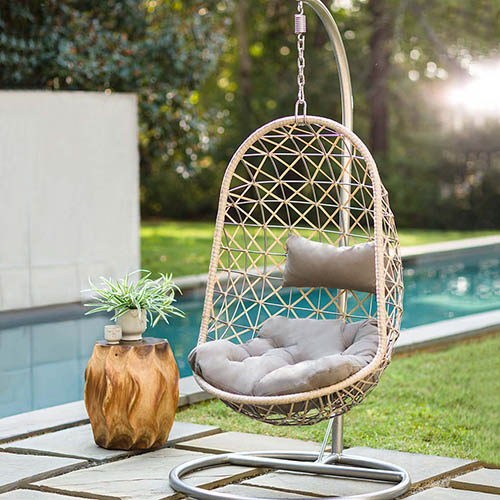 A garden scene with a swimming pool and a hanging egg-shaped chair on a metal stand with gray cushions and a small wooden table to the left of the frame.