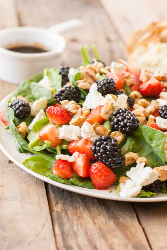 A vertical close up picture of a fresh spinach, cheese, and berry salad set on a wooden surface.