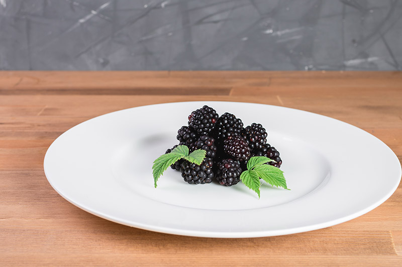 A close up of a white ceramic plate with fresh purple berries and a garnish of foliage, set on a wooden surface with a gray background.