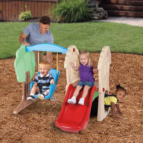 A close up of a family playing outdoors on the Little Tikes Hide and Seek Swing Set with lawn and a wooden fence in the background.