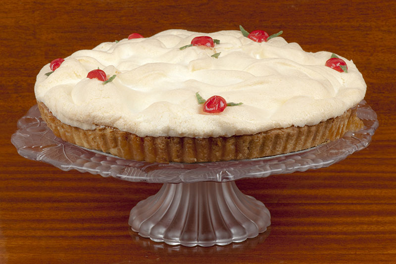 A close up of a lemon meringue pie on a glass cake stand set on a wooden surface.