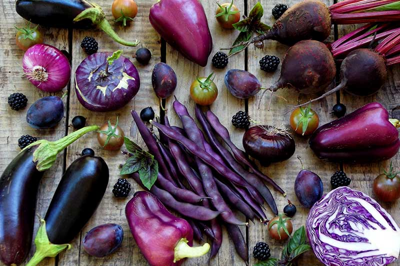 A close up of a variety of different purple vegetables and fruits set on a wooden surface.