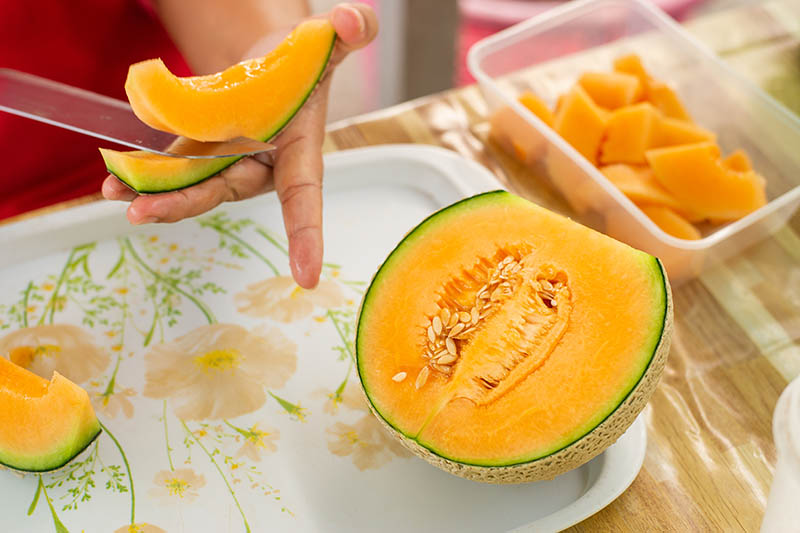 A close up of a hand from the left of the frame slicing a bright orange melon. The other half of the fruit is set on a plastic tray on a wooden surface.