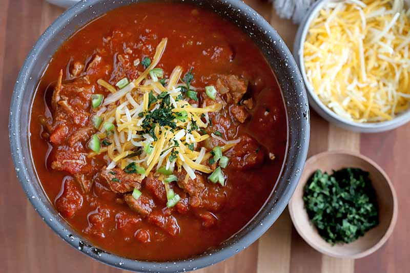 A close up top down picture of a bowl of chili, sprinkled with grated cheese and herbs, set on a wooden surface, with small bowls of cheese and herbs to the right of the frame in soft focus.