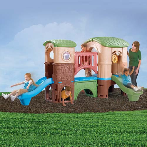 A plastic children's playhouse from Step2, called the Clubhouse Climber, set up on a lawn with blue sky in the background.