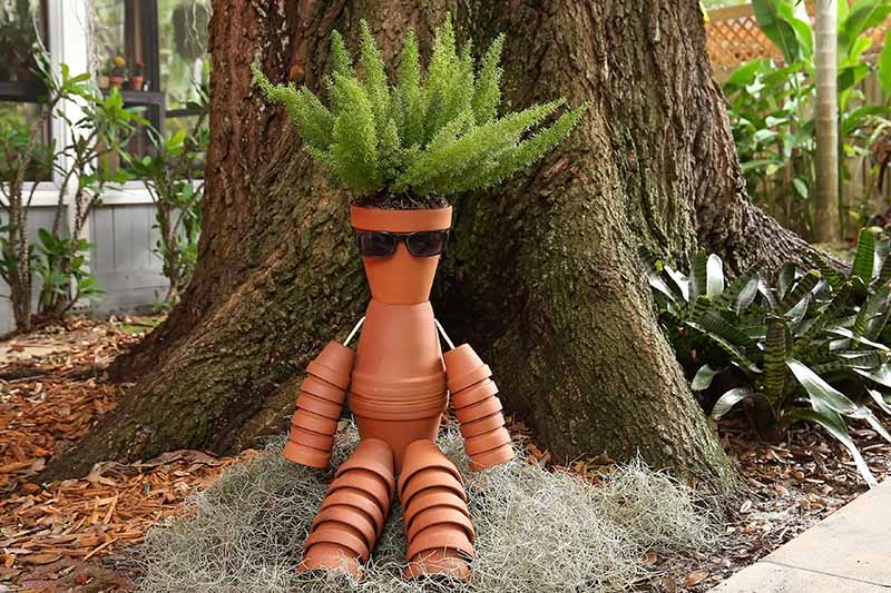 A close up of a collection of terra cotta pots in the shape of a person sitting on the ground in front of a tall tree, with asparagus fern growing out of the top pot to depict hair.