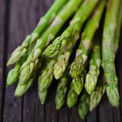 A close up of freshly harvested asparagus spears set on a wooden surface.