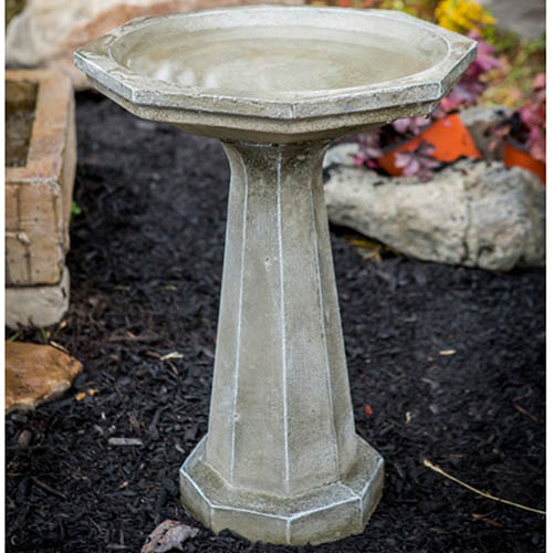A close up of the Athena Garden Cast Iron Octagon Bird Bath, set in the garden with flowers in the background.