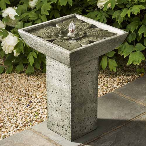 A close up of a small rustic concrete fountain set on the edge of a patio with bushes in the background.