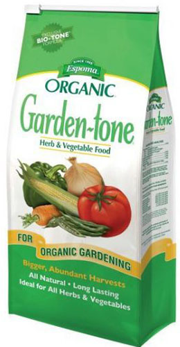 A close up of the green and white packaging of Espoma Garden tone fertilizer for organic gardens.