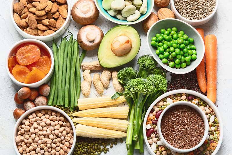 A close up of a variety of vegetables, nuts, seeds, and fruit as part of a healthy diet.