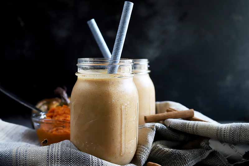 A close up of a jar of freshly made pumpkin pie smoothie with a straw in the top set on a gray and white fabric, pictured on a dark background.