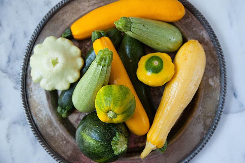 A close up top down picture of a metal plate with a number of different summer squash varieties, in green and yellow, set on a marble surface.