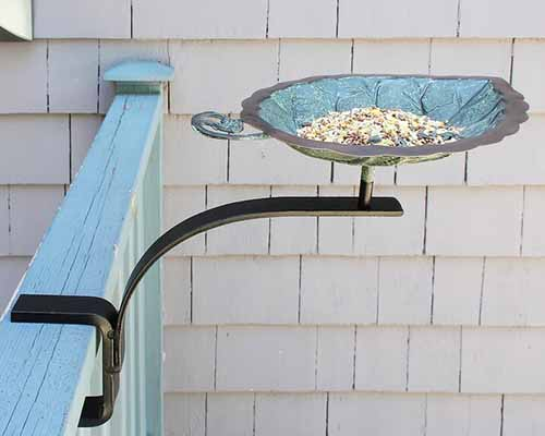A close up of a small leaf-shaped bird bath attached to a railing with a black metal bracket.