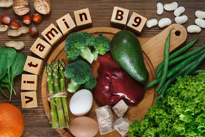 A circular wooden chopping board with a variety of vegetables and meat sources of vitamin B9. Around the outside is a wooden sign.