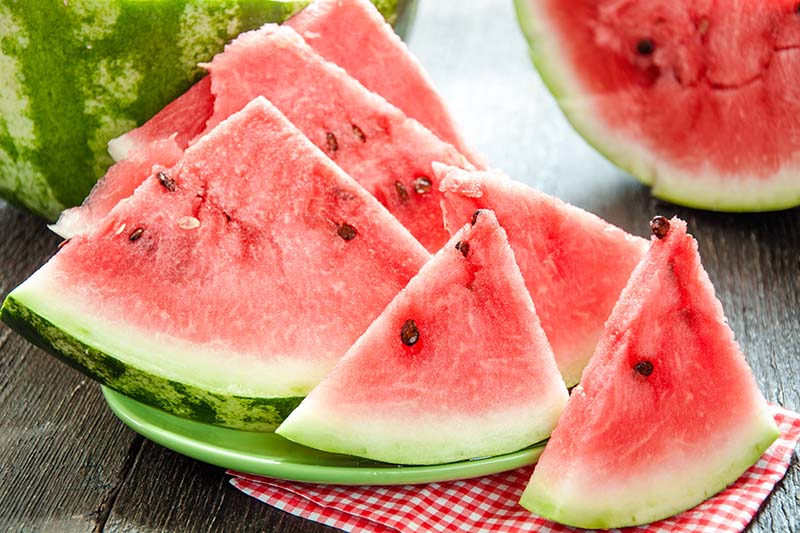 A close up of slices of watermelon set on a green plate on a wooden surface with fruit in soft focus in the background.