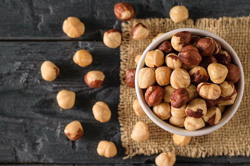 A close up, top down image of a small white bowl with freshly roasted hazelnuts spilling out over the dark gray surface, set on a burlap cloth.