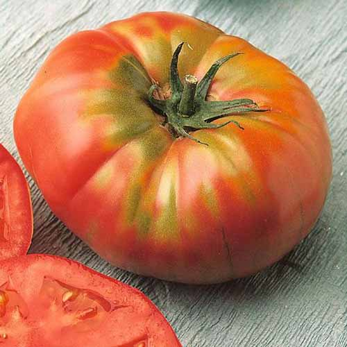 A close up of a freshly harvested 'Brandywine' tomato on a wooden surface.
