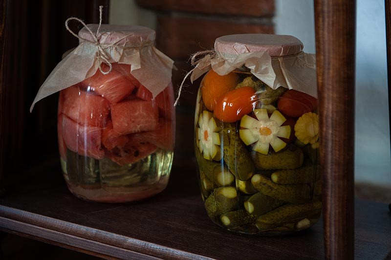 A close up horizontal image of two glass jars containing canned vegetables and fruits set on a wooden shelf.