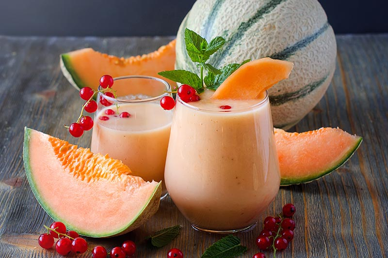 Horizontal image of sliced cantaloupe with red currants,and two glasses of an orange-colored fruit smoothie with a sprig of mint for garnish, on a wood surface with a whole melon with tan netting and prominent green sutures.