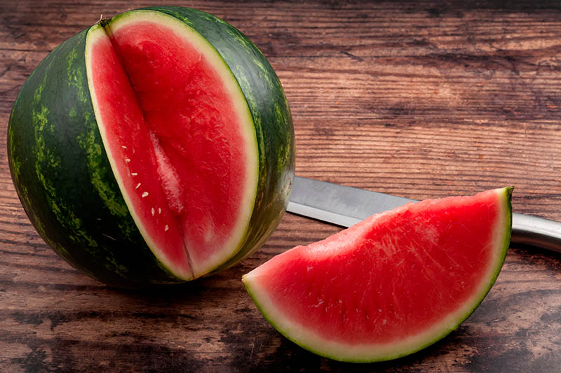 A close up of a large watermelon with a slice taken out of it, set on a wooden surface with a knife in the background.