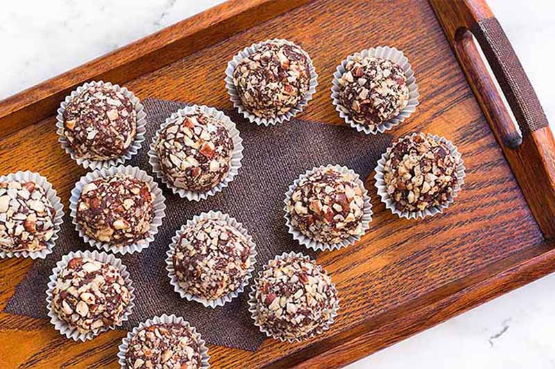 A horizontal, top down image of a wooden tray with freshly made chocolate truffles, set on a marble surface.