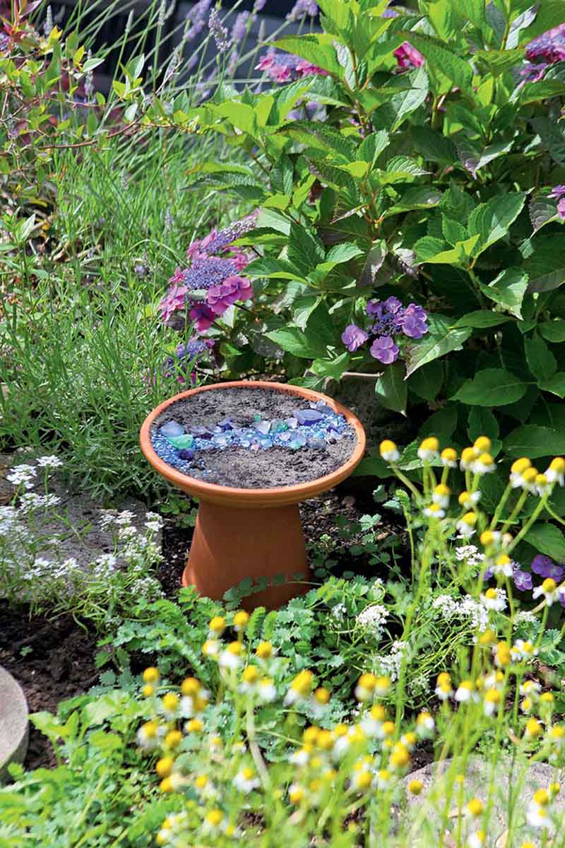 A vertical picture of a terra cotta bird bath filled with soil and blue glass, with a hydrangea in the background.