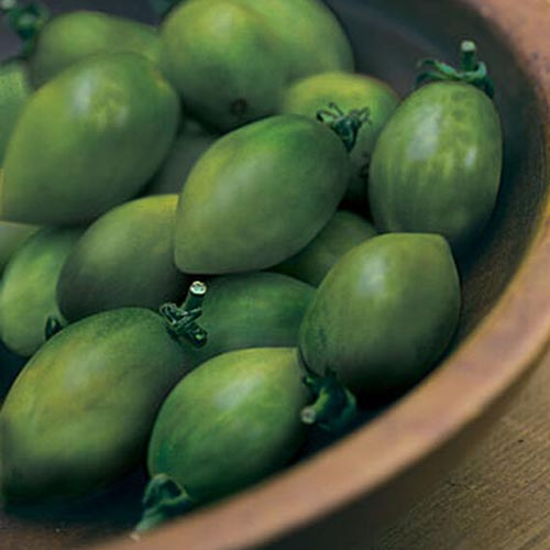 A close up of 'Green Envy' fruits, freshly harvested and placed in a wooden bowl.