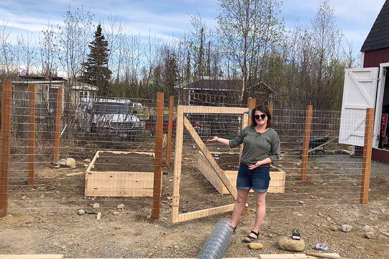 A woman stands outside a fenced garden area, with two raised beds in the background.