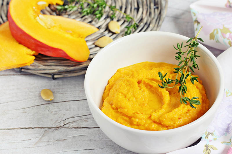 A close up of a small white bowl containing homemade pumpkin puree topped with a sprig of thyme, set on a wooden surface, with slices of squash on a basket in the background.