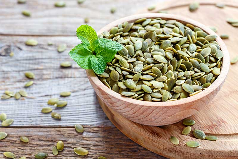 A close up horizontal image of a small wooden bowl containing green hulled pumpkin seeds, set on a wooden chopping board on a wooden table, with a sprig of mint.