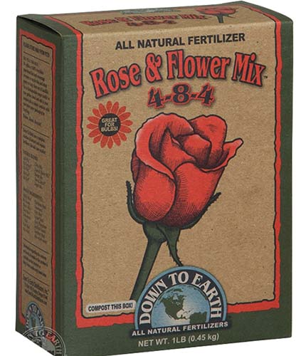 A close up of the packaging of Down to Earth Rose and Flower Mix fertilizer on a white background.