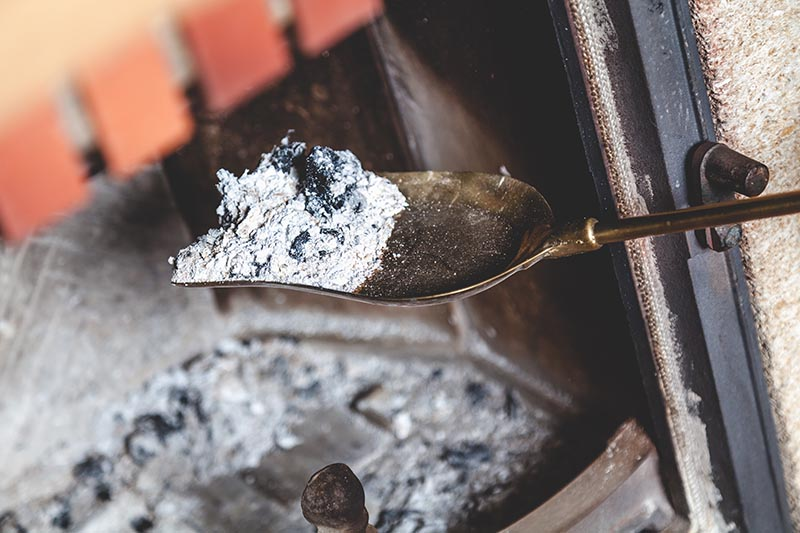 A close up of a trowel scooping wood ash out of a fireplace for placing on a compost pile.