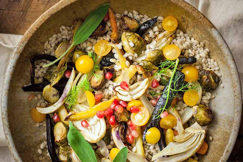 A close up top down picture of a fresh roasted vegetables with rice, topped with herbs.