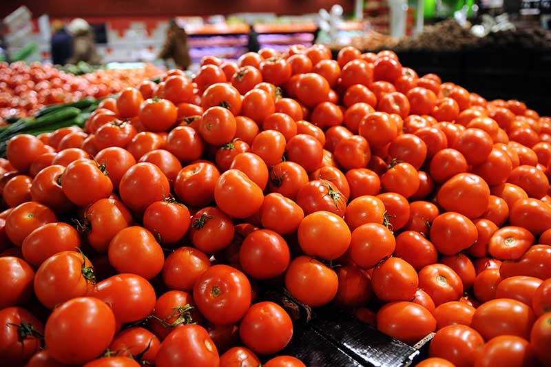 A large supermarket display of ripe red tomatoes, with shoppers and cabinetry in soft focus in the background.