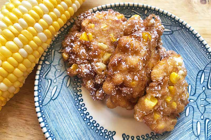 A close up, top down picture of a freshly made corn fritter set on a blue and white plate on a rustic wooden surface.