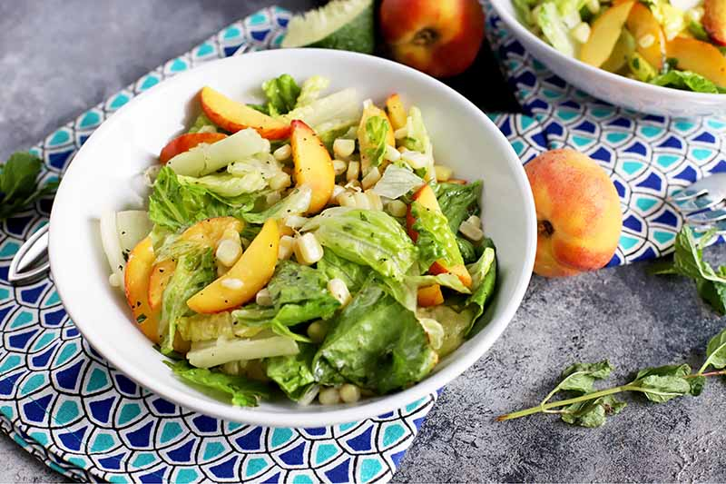 A close up of a white bowl with a peach and corn salad, set on a blue and white fabric on a dark gray surface, with fresh peaches and herbs scattered around.